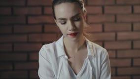 Donna arrogante con le labbra rosse che guardano con confidenza alla macchina fotografica sul copyspace del mattone stock footage
