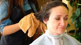 Donna asciutta i suoi capelli con un asciugamano dopo avere lavato la sua testa archivi video