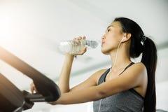 Donna asiatica in acqua potabile degli abiti sportivi Fotografie Stock