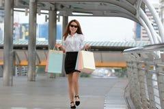 Donna asiatica allegra con i sacchetti della spesa variopinti che cammina sulla via della città Fotografia Stock Libera da Diritti