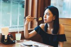 Donna asiatica attraente che si siede e che mangia alimento giapponese da solo nel ristorante fotografia stock libera da diritti