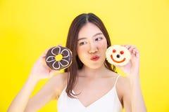 Donna asiatica attraente che tiene due guarnizioni di gomma piuma con l'espressione sveglia sopra fondo giallo immagine stock libera da diritti