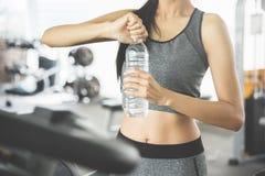 Donna asiatica in bottiglia della tenuta degli abiti sportivi di acqua Fotografia Stock