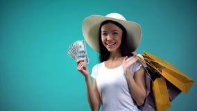 Donna asiatica in cappello del sole che tiene grande somma dei dollari e di molti sacchetti della spesa, prestito fotografia stock
