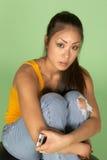 Donna asiatica che abbraccia le ginocchia con il telefono delle cellule Fotografia Stock