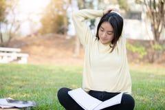 Donna asiatica che allunga e che si siede sull'erba verde dopo colto immagini stock libere da diritti