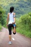 Donna asiatica che allunga le gambe Immagine Stock