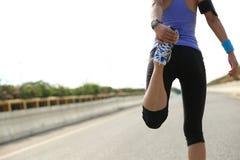 Donna asiatica che allunga le gambe Immagini Stock
