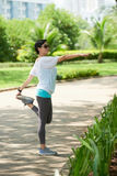Donna asiatica che allunga nel parco Immagini Stock Libere da Diritti
