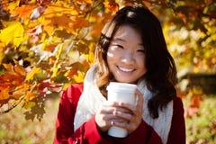 Donna asiatica che beve una bevanda calda Fotografie Stock