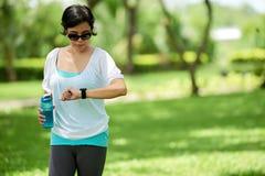 Donna asiatica che controlla polsino di forma fisica Fotografia Stock Libera da Diritti