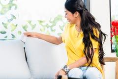 Donna asiatica che controlla prezzo del sofà in deposito Immagini Stock