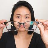 Donna asiatica che decolla i vetri fotografie stock libere da diritti