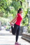Donna asiatica che fa allungando esercizio durante il treno trasversale all'aperto Fotografia Stock Libera da Diritti