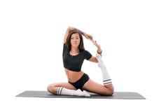 Donna asiatica che fa esercizio di allungamento o di yoga sulla stuoia Fotografie Stock Libere da Diritti
