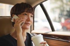 Donna asiatica che fa una telefonata in carrozza Immagini Stock