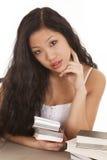 Donna asiatica che guarda con i libri Immagine Stock