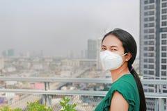Donna asiatica che indossa una maschera di protezione contro il PM 2 inquinamento atmosferico 5 nella citt? di Bangkok thailand fotografia stock