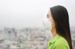 Donna asiatica che indossa una maschera di protezione contro il PM 2 inquinamento atmosferico 5 nella citt? di Bangkok thailand fotografia stock libera da diritti