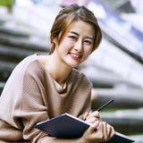 Donna asiatica che legge il libro Fotografia Stock