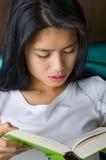 Donna asiatica che legge un libro fotografie stock