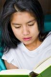 Donna asiatica che legge un libro immagini stock