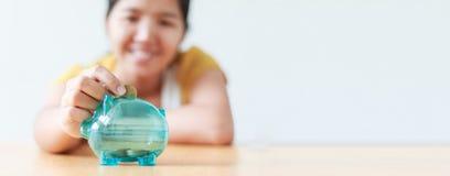Donna asiatica che mette la moneta dei soldi dentro per rimuovere la metafora s del porcellino salvadanaio immagine stock libera da diritti