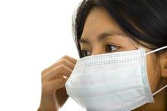 Donna asiatica che mette su una maschera di protezione Fotografie Stock Libere da Diritti