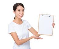 Donna asiatica che mostra la pagina in bianco della lavagna per appunti Immagini Stock