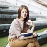 Donna asiatica che pensa con un libro Fotografia Stock