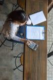 Donna asiatica che per mezzo del calcolatore per controllare il suo calcolo Fotografia Stock Libera da Diritti