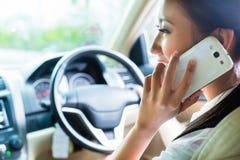 Donna asiatica che per mezzo del telefono che conduce automobile Immagine Stock