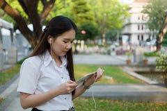 Donna asiatica che per mezzo della compressa ed ascoltando la musica Fotografia Stock Libera da Diritti
