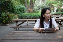 Donna asiatica che per mezzo della compressa ed ascoltando la musica Fotografia Stock