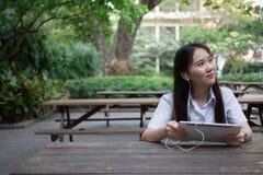 Donna asiatica che per mezzo della compressa ed ascoltando la musica Fotografie Stock Libere da Diritti