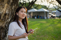Donna asiatica che per mezzo della compressa ed ascoltando la musica Fotografie Stock
