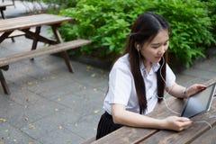 Donna asiatica che per mezzo della compressa ed ascoltando la musica Immagini Stock