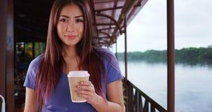 Donna asiatica che per mezzo dello smartphone invece della cabina telefonica mentre fuori viaggiando fotografia stock libera da diritti