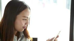 Donna asiatica che per mezzo di un telefono astuto video d archivio