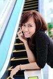 Donna asiatica che per mezzo di un telefono delle cellule Immagini Stock