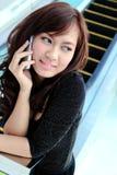 Donna asiatica che per mezzo di un telefono delle cellule Fotografia Stock Libera da Diritti