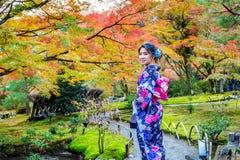 Donna asiatica che porta kimono tradizionale giapponese nel parco di autunno Immagine Stock