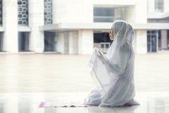Donna asiatica che prega per Allah nella moschea immagine stock
