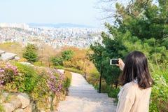 Donna asiatica che prende le immagini della vista aerea della città di Seoul con lo smartphone immagini stock libere da diritti
