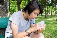Donna asiatica che prende nota con la penna ed il libro Fotografie Stock Libere da Diritti