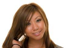 Donna asiatica che raddrizza capelli Fotografia Stock