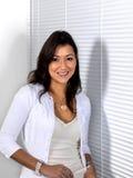Donna asiatica che si leva in piedi al lato delle tonalità bianche Fotografia Stock