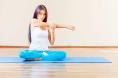 Donna asiatica che si scalda prima dell'esercizio di yoga dell'interno Fotografia Stock