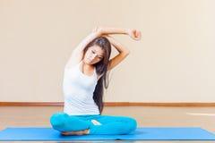 Donna asiatica che si scalda prima dell'esercizio di yoga dell'interno Fotografia Stock Libera da Diritti