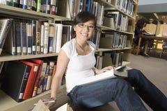 Donna asiatica che si siede nella biblioteca Fotografie Stock